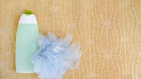Concepto del baño del balneario Toallita y champú puestos planos del fondo en la toalla Botella verde Espacio de la copia de la v imagen de archivo