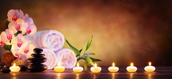 Concepto del balneario - piedras del masaje con las toallas y las velas imagen de archivo libre de regalías