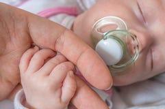 Concepto del bebé de la adopción El hombre es bebé conmovedor con la mano Fotografía de archivo