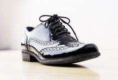 Concepto del calzado Imagen horizontal Zapatos de cuero clásicos femeninos negros en el escritorio Imagenes de archivo
