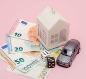 Concepto del casino, del juego y de la fortuna La casa y el coche modelo, juegos cortan en cuadritos y dinero euro en fondo rosad foto de archivo libre de regalías