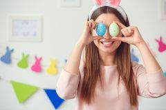 Concepto del celbration de pascua de la mujer joven en casa en los oídos de un conejito que sostienen los huevos que cubren ojos imagen de archivo libre de regalías