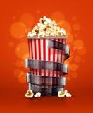Concepto del cine con el cubo de papel con la cinta de las palomitas y de la película Foto de archivo libre de regalías