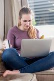 Concepto del comercio electrónico, mujer joven de pensamiento que compra en línea con la tarjeta de crédito Foto de archivo libre de regalías