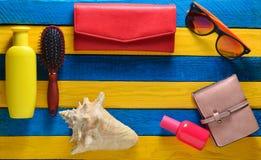 Concepto del complejo playero Accesorios femeninos de la playa en fondo de madera amarillo azul Shell, vidrios, monedero, sunbloc Imagenes de archivo