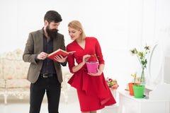 Concepto del conocimiento El hombre barbudo leyó el libro acerca de las plantas crecientes a la mujer, conocimiento Biblioteca de foto de archivo libre de regalías