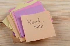 Concepto del consejo - etiqueta engomada con las palabras ' necesidad help' en fondo de madera Concepto de pedir ayuda fotos de archivo libres de regalías