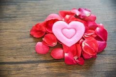 Concepto del corazón del amor de día de San Valentín/pila de pétalos de rosas con el corazón rosado adornado en la tabla de mader foto de archivo