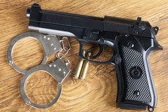 Concepto del crimen con la arma de mano, las esposas y las balas en un fondo de madera Foto de archivo