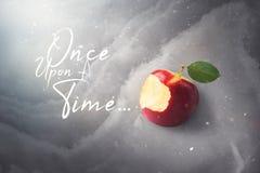 Concepto del cuento del cuento de hadas con la manzana roja mordida envenenada que pone encendido imágenes de archivo libres de regalías