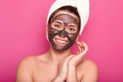 Concepto del cuidado de piel La mujer joven satisfecha con sonrisa dentuda, tiene máscara facial del cocholate, aislada en fondo  foto de archivo