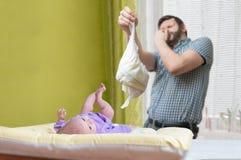 Concepto del cuidado del bebé El papá del od del padre está cambiando el pañal stinky Foto de archivo libre de regalías