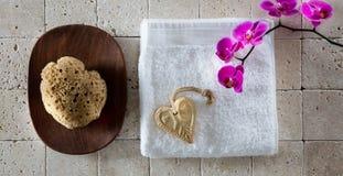 Concepto del cuidado del cuerpo con la esponja, el jabón de las tarjetas del día de San Valentín y la toalla naturales del algodó Fotos de archivo