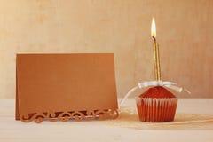 Concepto del cumpleaños con la magdalena y la vela al lado de la tarjeta de felicitación Foto de archivo libre de regalías
