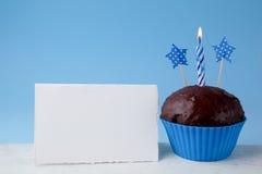 Concepto del cumpleaños con la magdalena y la vela al lado de la tarjeta de felicitación vacía en fondo azul Fotografía de archivo