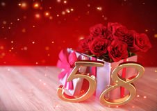 Concepto del cumpleaños con las rosas rojas en regalo en el escritorio de madera cincuenta-octavo 58.o 3d rinden Imagen de archivo