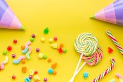 Concepto del cumpleaños con los dulces y los sombreros del partido en copyspace amarillo de la opinión superior del fondo Fotografía de archivo
