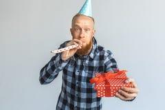 Concepto del cumpleaños Hombre maduro en la situación del casquillo aislado en el regalo de donante gris al cuerno del partido de foto de archivo