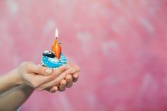 Concepto del cumpleaños, poca torta con una vela en manos Imágenes de archivo libres de regalías