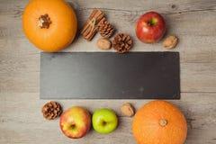 Concepto del Día de Acción de Gracias con la pizarra y la calabaza en la tabla de madera Fotos de archivo