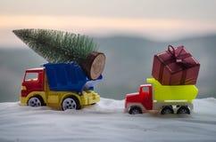 Concepto del día de fiesta del Año Nuevo Coche miniatura con el árbol de abeto en bosque del invierno Nevado, o coche del juguete Foto de archivo