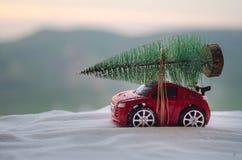 Concepto del día de fiesta del Año Nuevo Coche miniatura con el árbol de abeto en bosque del invierno Nevado, o coche del juguete Imágenes de archivo libres de regalías