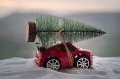 Concepto del día de fiesta del Año Nuevo Coche miniatura con el árbol de abeto en bosque del invierno Nevado, o coche del juguete Fotos de archivo