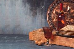 Concepto del día de fiesta de la pascua judía con el vino, el matzoh y la placa del seder sobre fondo rústico oscuro Fotografía de archivo libre de regalías