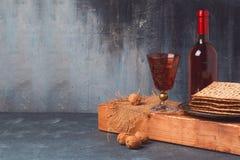 Concepto del día de fiesta de la pascua judía con el vino y el matzoh en el tablero de madera Imagen de archivo