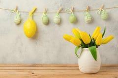 Concepto del día de fiesta de Pascua con el colgante de las decoraciones de las flores y de los huevos del tulipán Imagenes de archivo