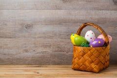 Concepto del día de fiesta de Pascua con la cesta de los huevos sobre fondo rústico de madera Foto de archivo libre de regalías