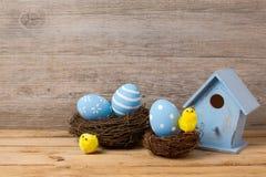 Concepto del día de fiesta de Pascua con la decoración de los huevos, la casa del pájaro y la jerarquía hechas a mano Fotos de archivo libres de regalías