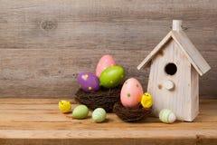 Concepto del día de fiesta de Pascua con la decoración de los huevos, la casa del pájaro y la jerarquía sobre fondo rústico de ma Imagenes de archivo