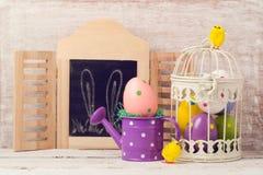 Concepto del día de fiesta de Pascua con la decoración del huevo en jaula de pájaros Foto de archivo