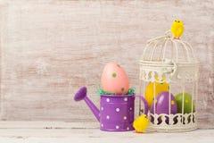 Concepto del día de fiesta de Pascua con la decoración del huevo en jaula de pájaros Imagen de archivo