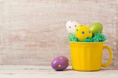 Concepto del día de fiesta de Pascua con la decoración del huevo en taza amarilla Foto de archivo libre de regalías