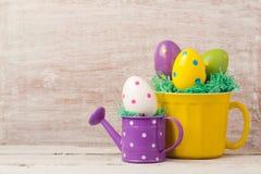 Concepto del día de fiesta de Pascua con la decoración del huevo en taza y regadera amarillas Imagen de archivo libre de regalías