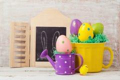 Concepto del día de fiesta de Pascua con la decoración, la taza y la regadera pintadas de los huevos Fotos de archivo