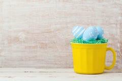 Concepto del día de fiesta de Pascua con la taza y los huevos pintados Fotografía de archivo libre de regalías