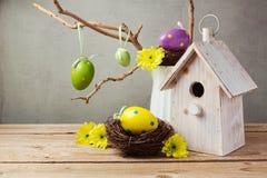 Concepto del día de fiesta de Pascua con las decoraciones de los huevos y la casa del pájaro Imágenes de archivo libres de regalías