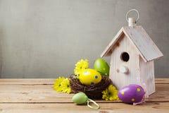 Concepto del día de fiesta de Pascua con las decoraciones de los huevos y la casa del pájaro Foto de archivo libre de regalías