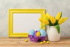 Concepto del día de fiesta de Pascua con las flores del tulipán, las decoraciones de los huevos y el marco en blanco de la foto Fotos de archivo libres de regalías