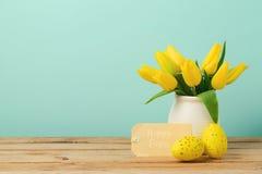 Concepto del día de fiesta de Pascua con las flores del tulipán, las decoraciones de los huevos y la etiqueta de papel Fotografía de archivo libre de regalías