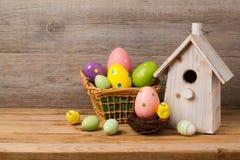 Concepto del día de fiesta de Pascua con los huevos y la casa del pájaro sobre fondo de madera Imágenes de archivo libres de regalías