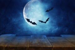 Concepto del día de fiesta de Halloween Vacie la tabla rústica delante del cielo nocturno asustadizo y brumoso con los palos negr foto de archivo