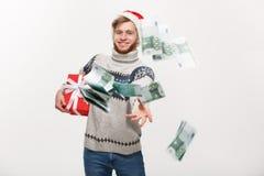 Concepto del día de fiesta - hombre joven de la barba que sostiene el regalo de la Navidad y que lanza el dinero a la cámara fotos de archivo libres de regalías