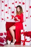 Concepto del día de fiesta - mujer magnífica en el vestido rojo largo que se sienta en el de Fotografía de archivo