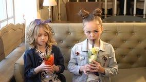 Concepto del día de fiesta y del ocio las niñas bonitas beben los cócteles con la paja en un restaurante, café HD lleno metrajes