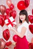 Concepto del día de tarjeta del día de San Valentín - caja de regalo hermosa joven de la tenencia de la mujer sobre fondo rojo de imagenes de archivo
