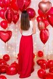 Concepto del día de tarjeta del día de San Valentín - opinión trasera la mujer hermosa con los globos en forma de corazón imagen de archivo libre de regalías
